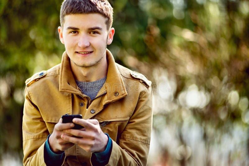 Atrakcyjny młody człowiek używa telefon komórkowego zdjęcie stock