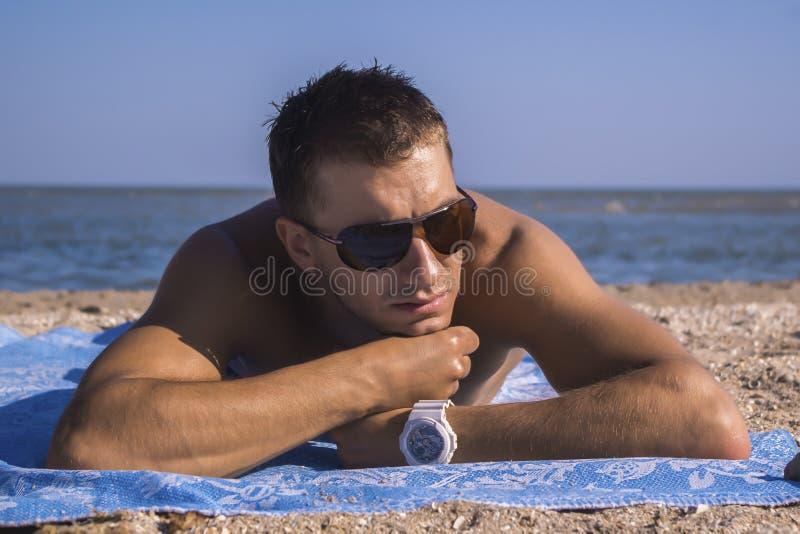 Atrakcyjny młody człowiek w okularach przeciwsłonecznych i bielu zegarze obrazy stock