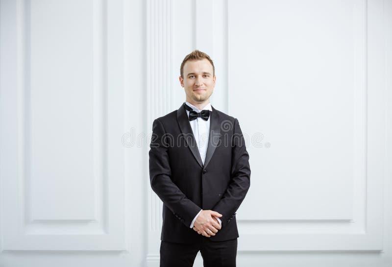 Atrakcyjny młody człowiek w smokingu uśmiechniętym i patrzeje kamerę fotografia royalty free