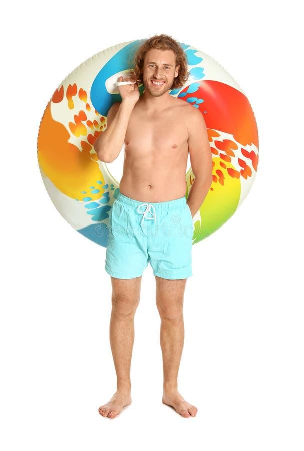 Atrakcyjny młody człowiek w swimwear z kolorowym nadmuchiwanym pierścionkiem fotografia royalty free