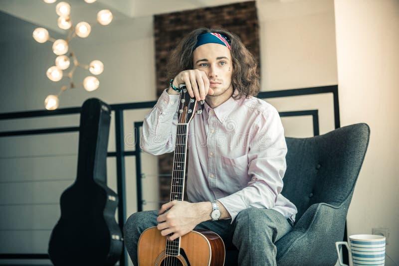 Atrakcyjny młody człowiek z przykrością patrzeje na zewnątrz okno z niebieskimi oczami zdjęcie royalty free