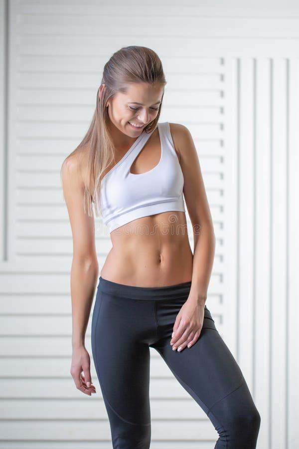 Atrakcyjny młody dorosły w sportswear pozuje na białym tle Seksowna i zmysłowa brunetki kobieta z doskonalić ciałem zdjęcia royalty free