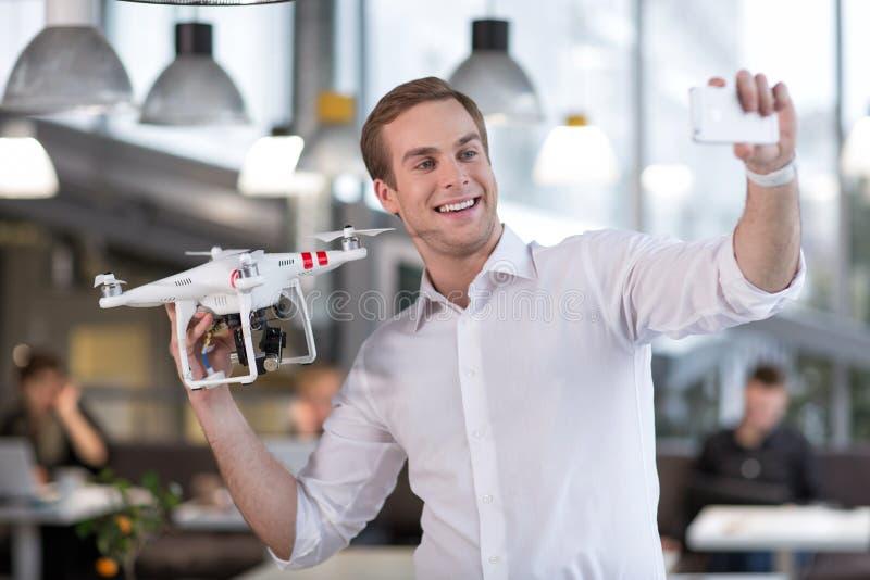 Atrakcyjny młody facet fotografuje z quadrocopter zdjęcia stock