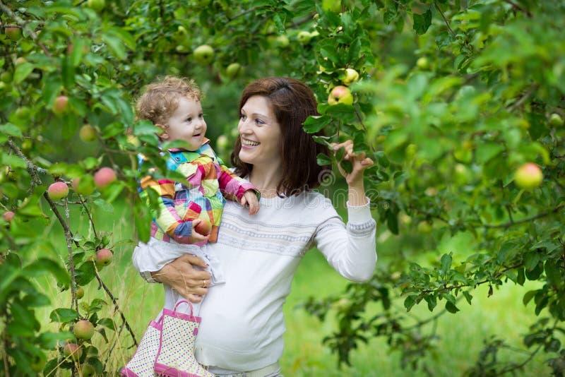 Atrakcyjny młody kobieta w ciąży trzyma jej dziecko córki zdjęcie stock