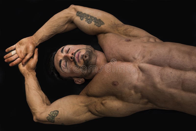 Atrakcyjny młody mięśnia mężczyzna kłaść na podłoga obrazy stock
