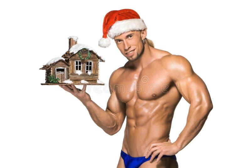 Atrakcyjny młody mięśnia mężczyzna ono uśmiecha się w Święty Mikołaj obrazy stock