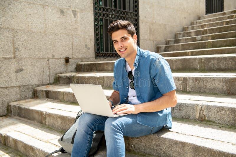 Atrakcyjny młody nowożytny mężczyzna pracuje z komputerem w mieście na outside schodkach fotografia stock