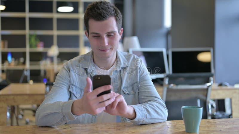 Atrakcyjny młody projektant korzystający ze smartfonu w nowoczesnym biurze fotografia royalty free