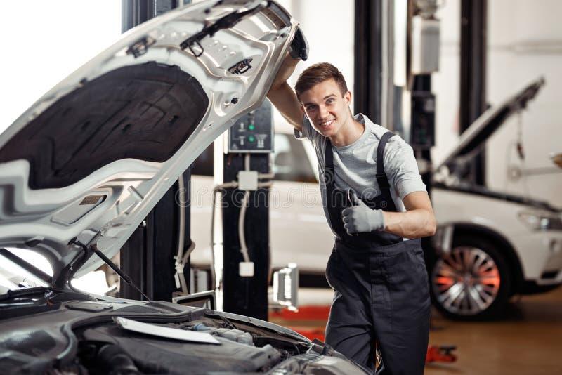 Atrakcyjny młody samochodowy mechanik jest uśmiechnięty: samochodu utrzymanie i usługa zdjęcia royalty free