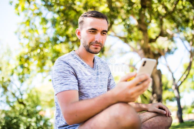 Atrakcyjny młody uśmiechnięty mężczyzna używa telefon w jawnym parku zdjęcia stock