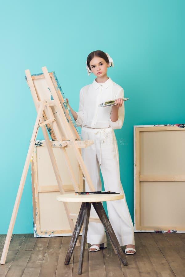 atrakcyjny nastoletni artysty obraz na sztaludze z muśnięciem i paletą obraz stock
