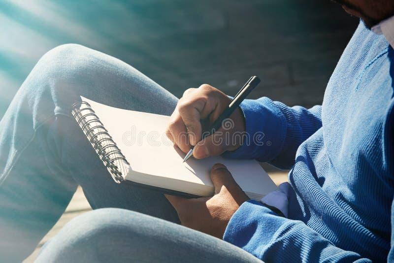 Atrakcyjny niezobowiązująco ubierający młody amerykański afrykański mężczyzna robi notatkom w copybook ochraniaczu Studencki narz zdjęcia stock