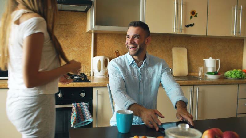 Atrakcyjny pary spotkanie w kuchennym wczesnym poranku i używać cyfrowego pastylka komputer dla ogólnospołecznego medialnego surf zdjęcie royalty free