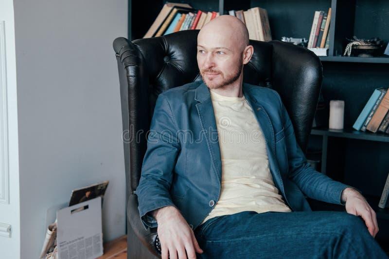 Atrakcyjny pomyślny dorosły łysy uśmiechnięty mężczyzna z brodą w kostiumu obsiadaniu w krześle w jego biurze przeciw książki ści obraz royalty free