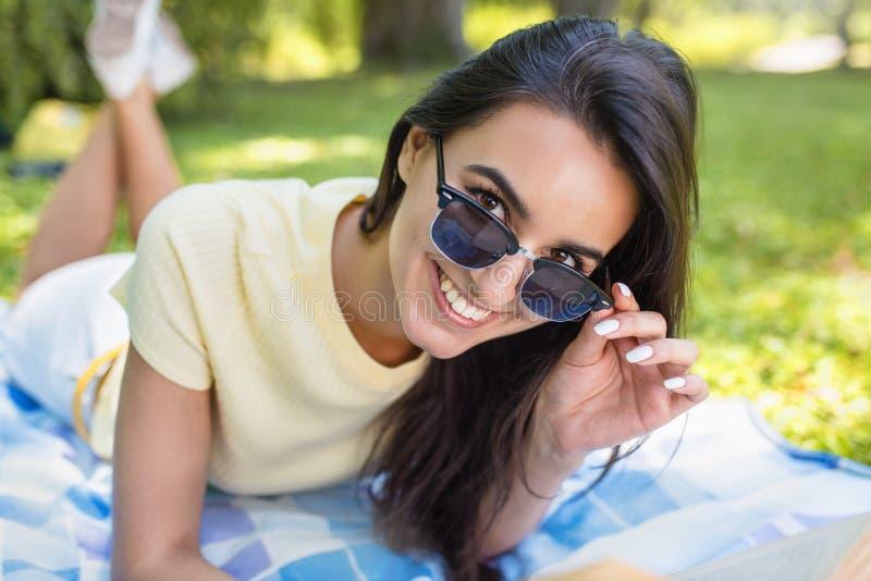 Atrakcyjny portret młodej brunetki ono uśmiecha się i jest ubranym Kaukascy żeńscy okulary przeciwsłoneczni kłama na błękitnej sz fotografia royalty free