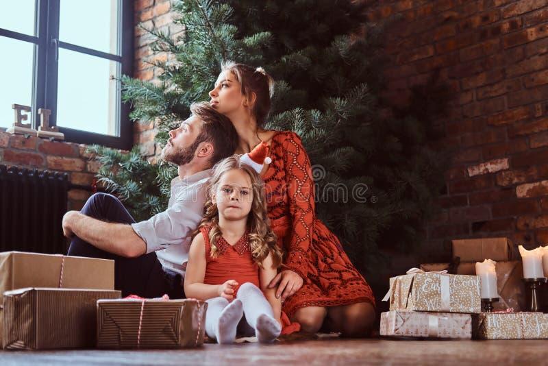 Atrakcyjny rodzinny obsiadanie na podłodze otaczającej prezentami obok choinki w domu zdjęcie stock
