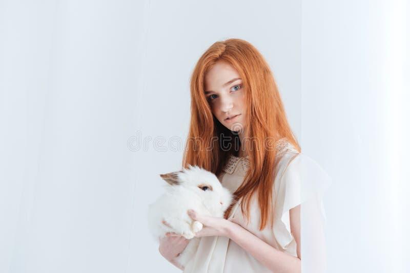 Atrakcyjny rudzielec kobiety mienia królik fotografia royalty free
