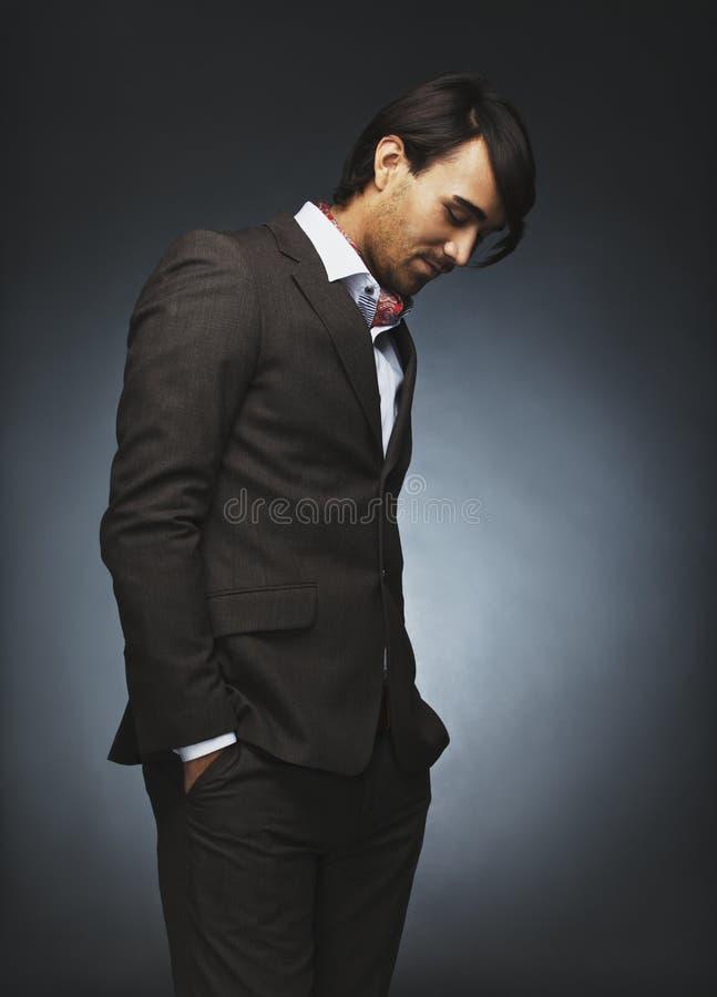 Atrakcyjny samiec model stoi niezobowiązująco na czarnym tle zdjęcia royalty free