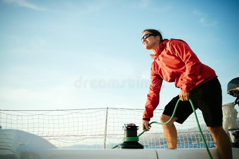 Atrakcyjny silny kobiety żeglowanie z jej łodzią zdjęcie stock