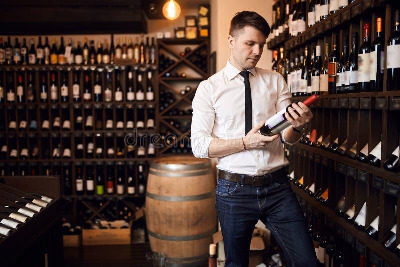 Atrakcyjny sommelier jest ubranym białą koszula i spodnia stoi w wino sklepie fotografia stock