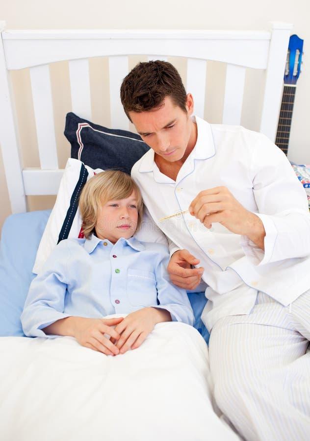 Download Atrakcyjny Sprawdzać Ojciec Jego S Syna Temperatura Zdjęcie Stock - Obraz złożonej z ojciec, póżniej: 13341698