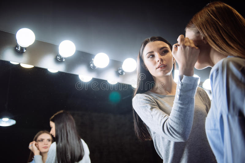 Atrakcyjny sprawny visagiste kładzenie na eyeshadow makeup obrazy royalty free