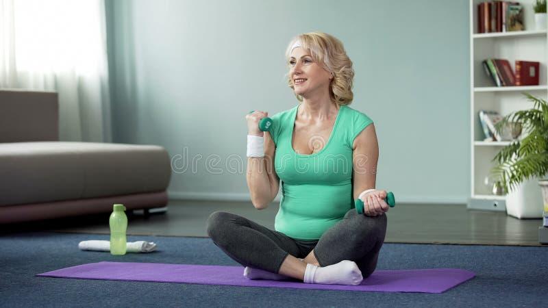 Atrakcyjny starszy damy obsiadanie na podłodze i podnośnych dumbbells, domowy trening zdjęcie stock