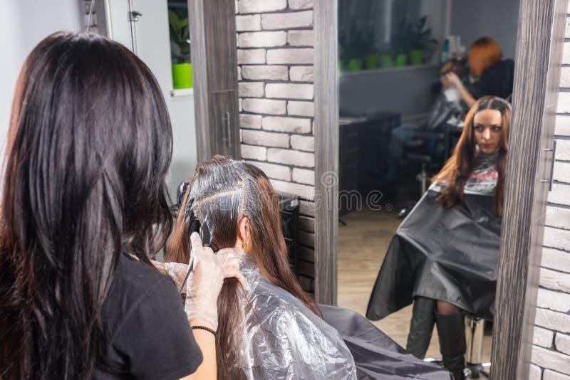 Atrakcyjny stylista podczas procesu barwiarstwo włosy młoda kobieta fotografia royalty free