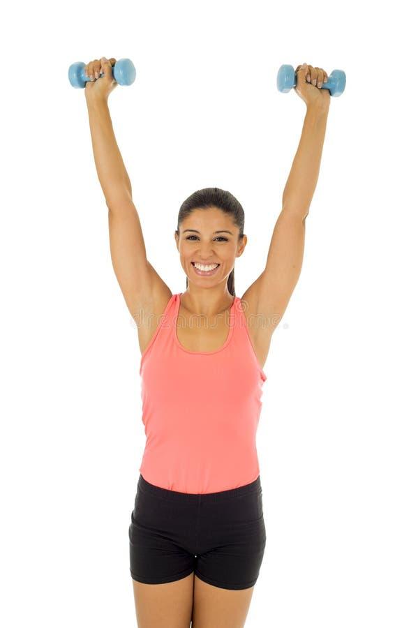 Atrakcyjny szczęśliwy łaciński kobiety mienia ciężaru dumbbell robi sprawność fizyczna treningowi zdjęcie stock