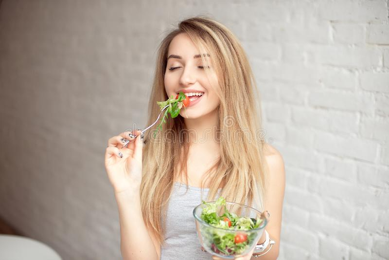 Atrakcyjny szczęśliwy kobiety mienia puchar świeżego warzywa sałatka w rękach je z rozwidleniem, enjoing zdrowy jedzenie obraz stock
