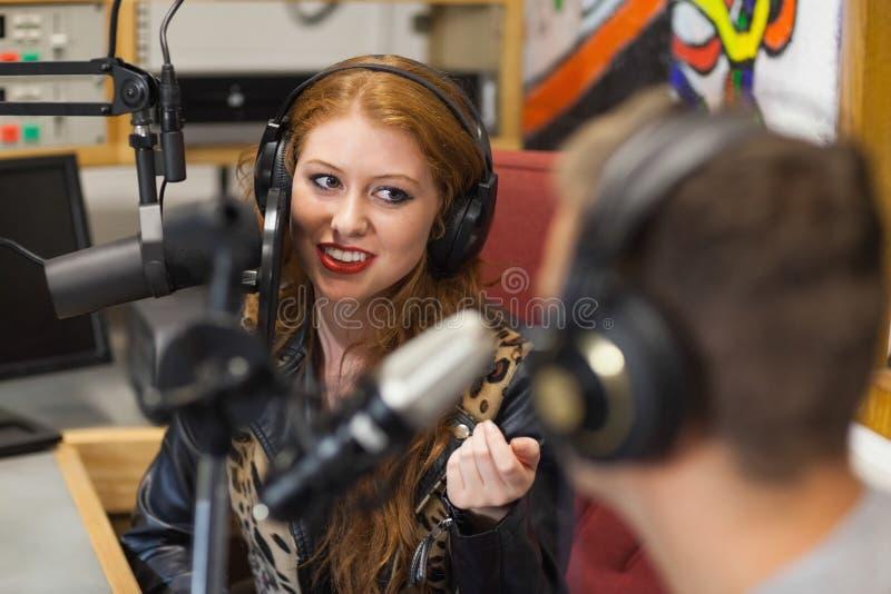 Atrakcyjny szczęśliwy radiowy gospodarz przeprowadza wywiad gościa fotografia stock