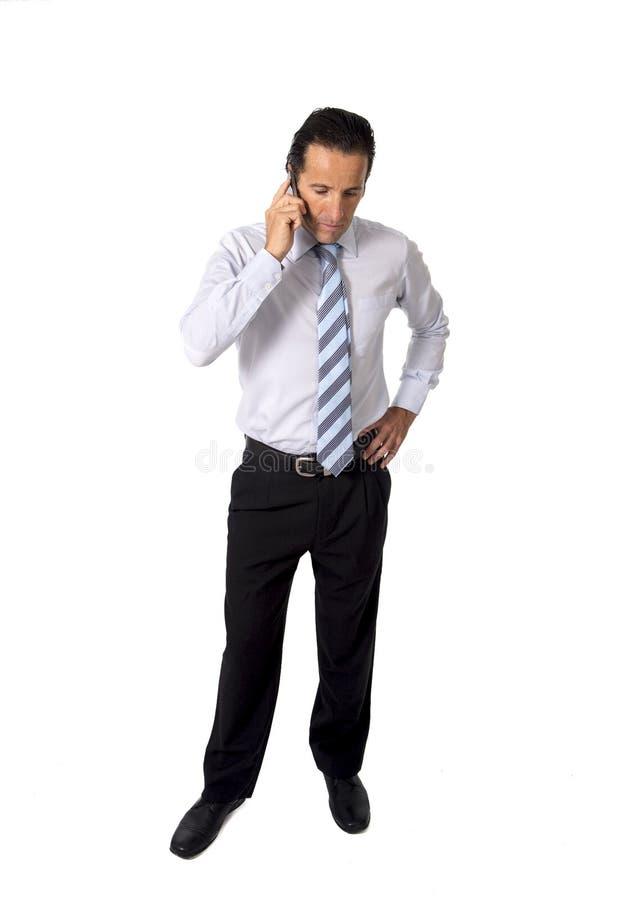 Atrakcyjny ufny starszy Latynoski biznesmen opowiada biznes na telefon komórkowy pozyci przy pracą fotografia royalty free