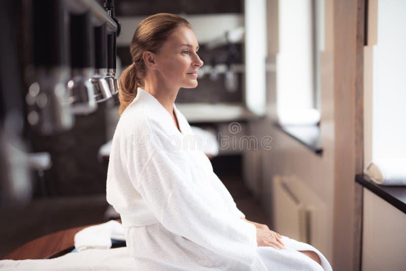Atrakcyjny w średnim wieku damy obsiadanie przy wellness centrum obrazy stock