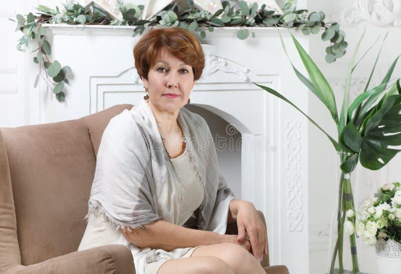 Atrakcyjny w średnim wieku kobiety obsiadanie w krześle obrazy stock