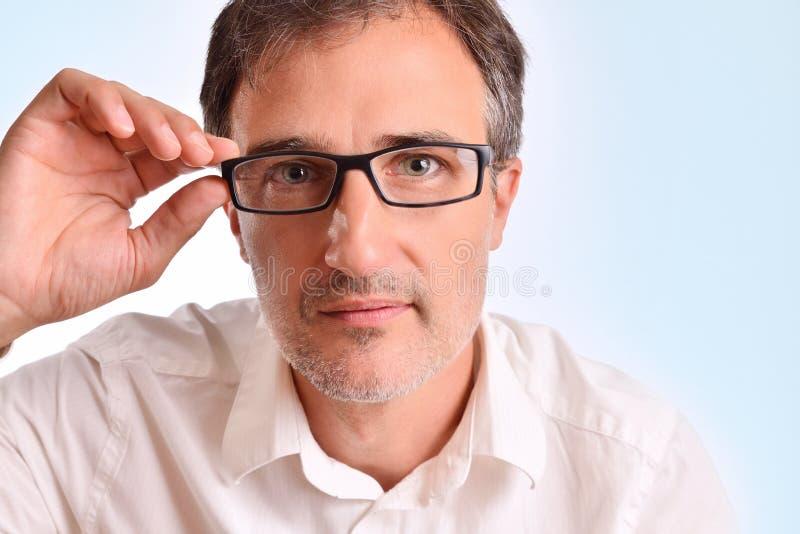 Atrakcyjny w średnim wieku mężczyzna przystosowywa szkieł gapić się obrazy stock