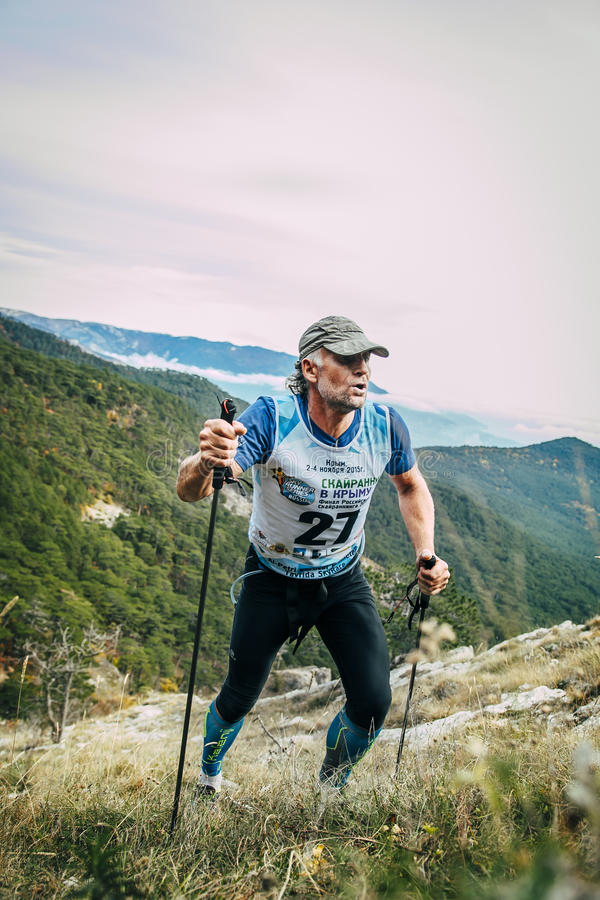 Atrakcyjny w średnim wieku mężczyzna wspina się górę z północnymi chodzącymi słupami zdjęcia royalty free