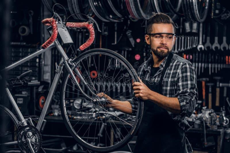 Atrakcyjny zadumany mężczyzna w ochronnych szkłach naprawia bicykl przy jego swój warsztatem obraz stock