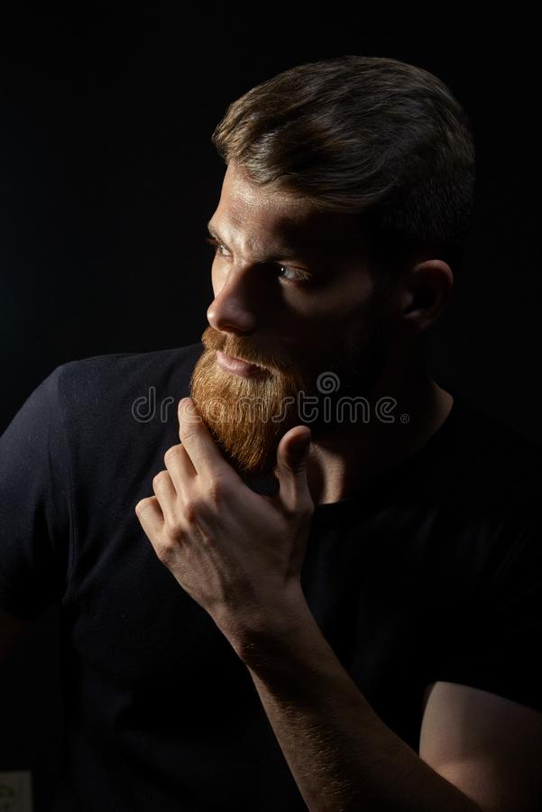 Atrakcyjny zadumany młody człowiek patrzeje w dystansowego uderzanie jego brodę fotografia stock