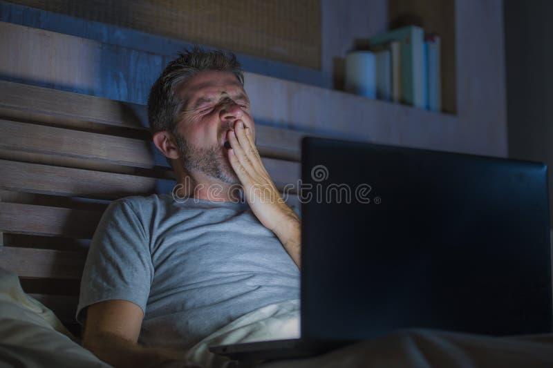Atrakcyjny zmęczony i zaakcentowany workaholic mężczyzna pracuje nocny skołowanego na łóżkowy ruchliwie z laptopu ziewający czuci zdjęcie stock