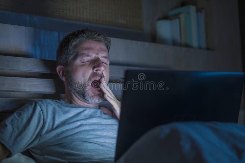 Atrakcyjny zmęczony i zaakcentowany workaholic mężczyzna pracuje nocny skołowanego na łóżkowy ruchliwie z laptopu ziewający czuci zdjęcie royalty free