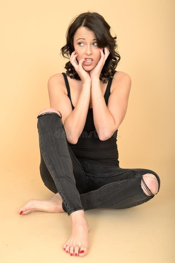 Atrakcyjny Zmartwiony Niespokojny młodej kobiety obsiadanie na podłoga fotografia stock