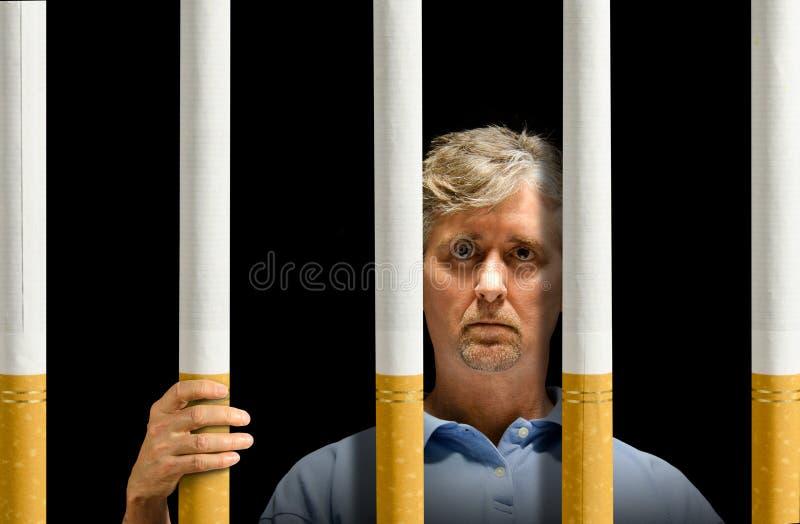 Atrapado por la prisión del apego de nicotina de los cigarrillos imagen de archivo