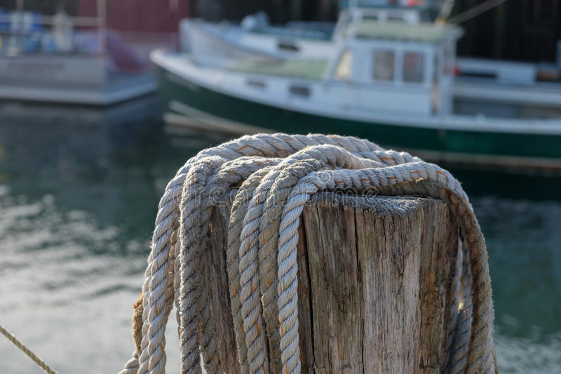 Atraque la cuerda lateral de la guindaleza del cáñamo lista para ser utilizado para amarrar el barco de la langosta foto de archivo