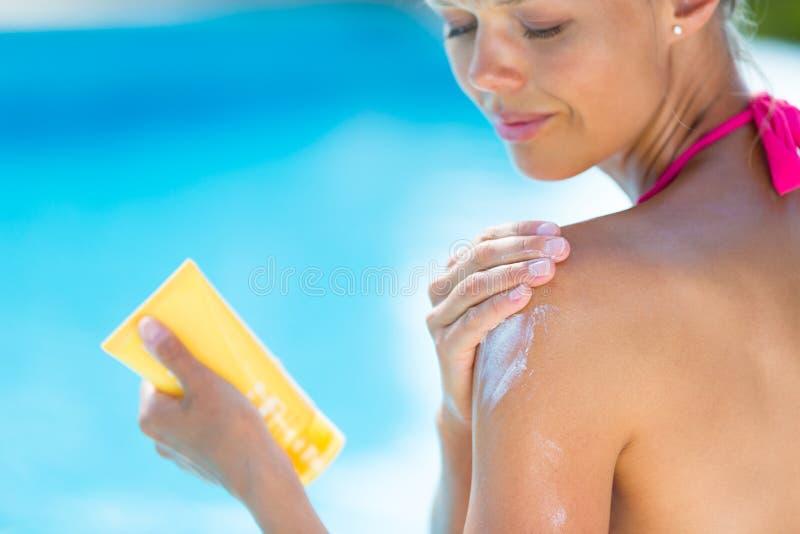 Atrativo, jovem mulher com a pele saudável que aplica o suncream fotografia de stock