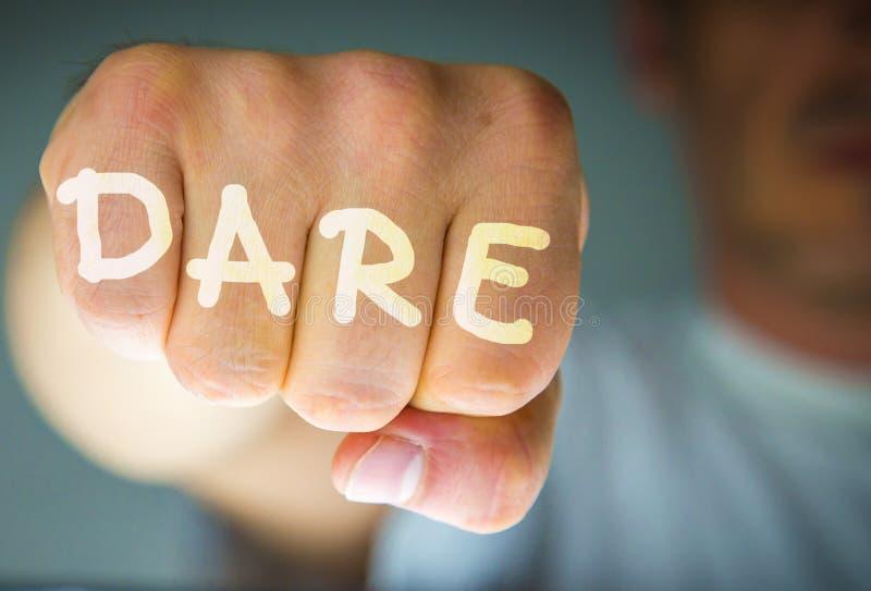 ATREVIMIENTO escrito en el puño enojado de los man's imagen de archivo libre de regalías