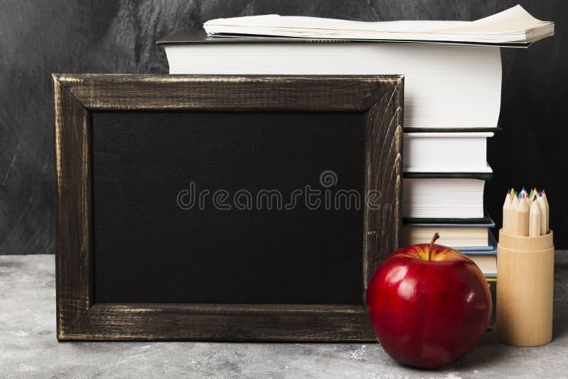 Atributos da escola - a placa preta, livros, coloriu lápis, noteboo fotografia de stock royalty free