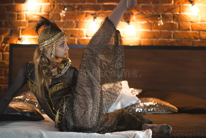 Atriz bonita do circo que executa a dança com uma serpente na cama foto de stock