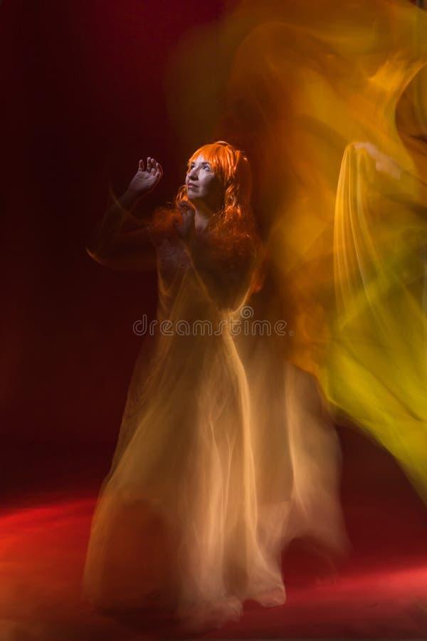 Atriz fêmea idosa com dança alaranjada do cabelo no vestido branco com mostra clara com luzes amarelas, alaranjadas e verdes ao r fotos de stock