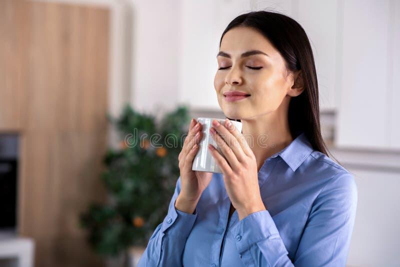 Atrractive tillfredsställde kvinnan som dricker hennes kaffe royaltyfri foto