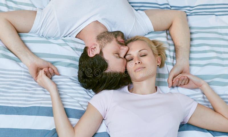 Att älska par som ligger på säng, heads tillsammans royaltyfri fotografi